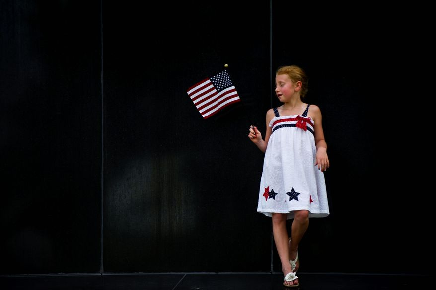 Anne Byrd Fickling, 7, of Fredericksburg, Va., waits for the sun to set and the fireworks to start at the base of the Iwo Jima Memorial in Arlington. (Drew Angerer/The Washington Times)