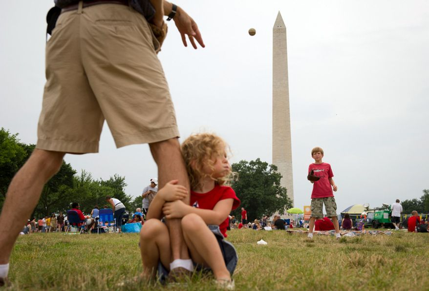 Deryk Jeter (left) plays catch with his 10-year-old son, Henry (right), while his 4-year-old daughter, Margaret, grabs onto his leg as they celebrate Independence Day on the National Mall in Washington on Monday, July 4, 2011. (Rod Lamkey Jr./The Washington Times)