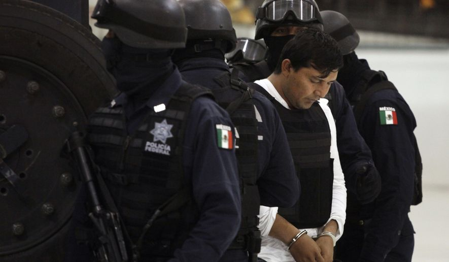 "Mexican Federal Police agents escort Jesus Enrique Rejon Aguilar, alias ""El Mamito,"" to his presentation to the media in Mexico City on Monday, July 4, 2011. Police believe he is connected with the killing of a U.S. Immigration and Customs Enforcement agent in February. (AP Photo/Alexandre Meneghini)"