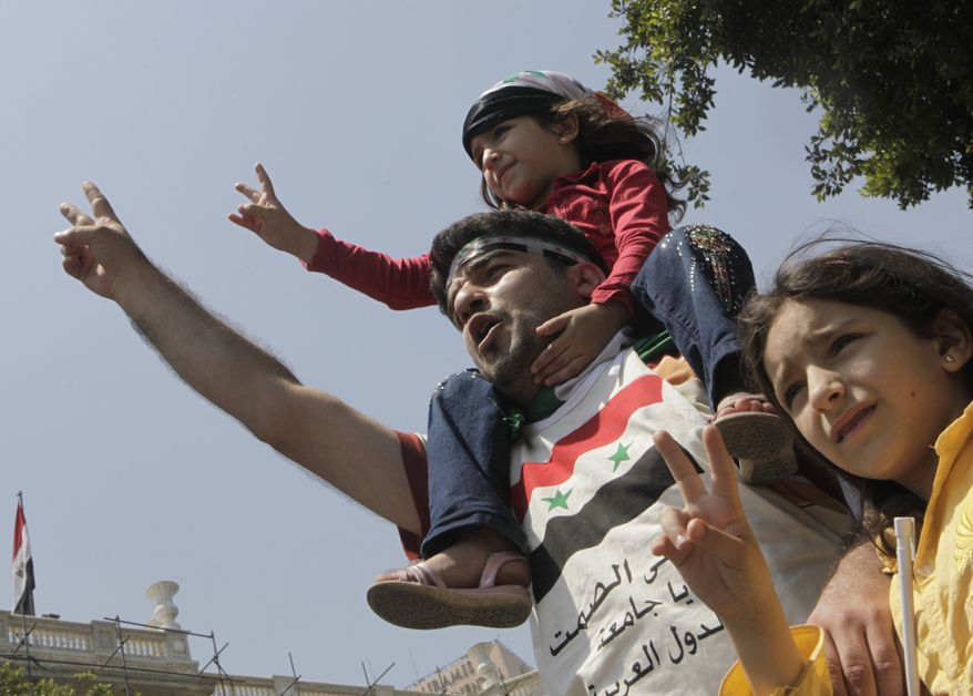 A Syrian family shouts slogans against Syrian President Bashar Asssad as they wear Syrian independence flags during a protest outside the Arab League headquarters in Cairo on Sunday, July 3, 2011. (AP Photo/Amr Nabil)