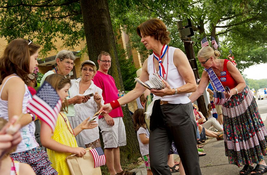 D.C. Council member Mary Cheh (center) hands out copies of the U.S. Constitution to spectators along MacArthur Boulevard Northwest during the annual Palisades July Fourth parade. (Barbara L. Salisbury/The Washington Times)
