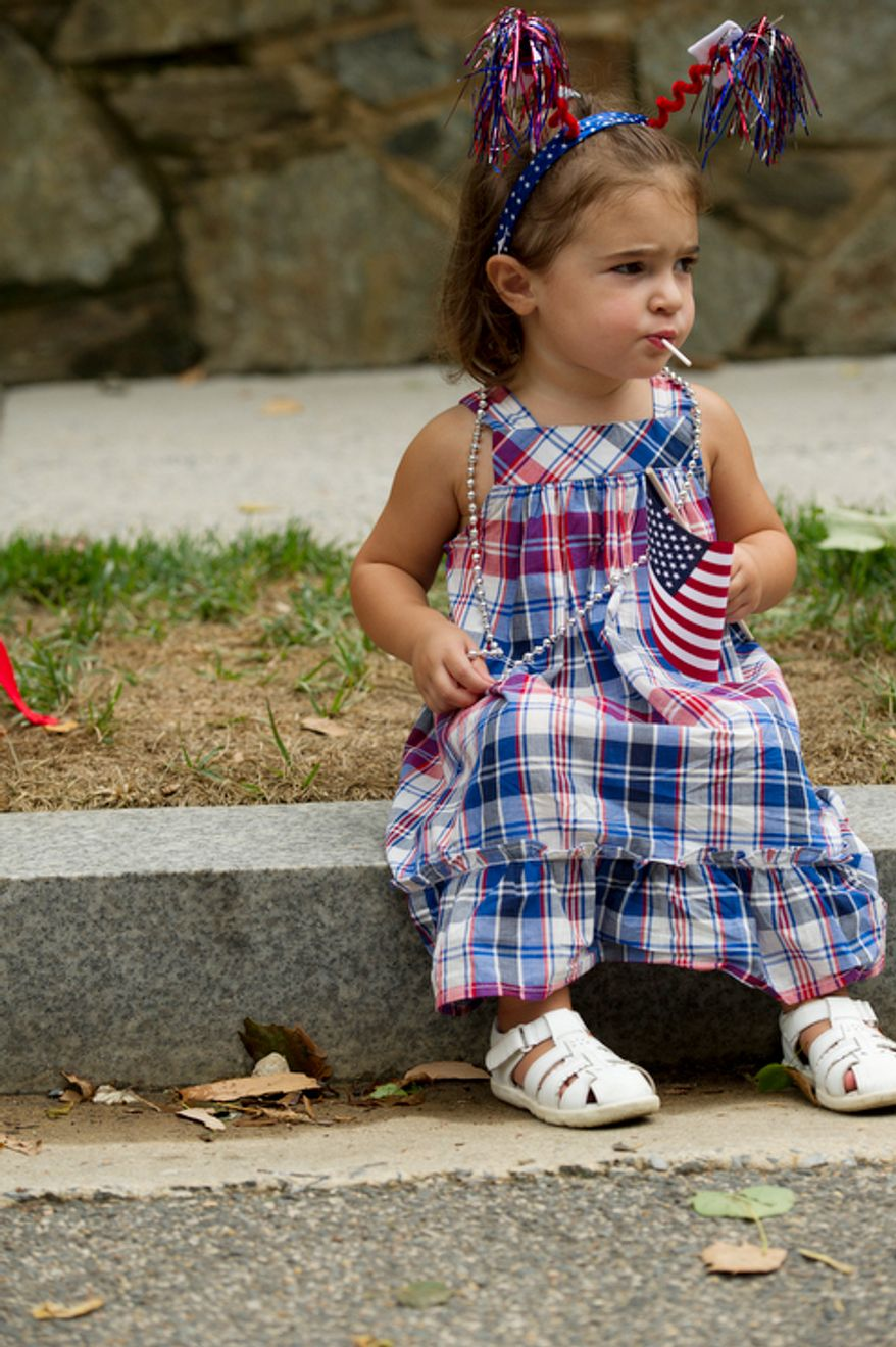 Two-year-old Annie DelGuercio of Washington is patriotic in red, white and blue while watching the Palisades July Fourth parade. (Barbara L. Salisbury/The Washington Times)