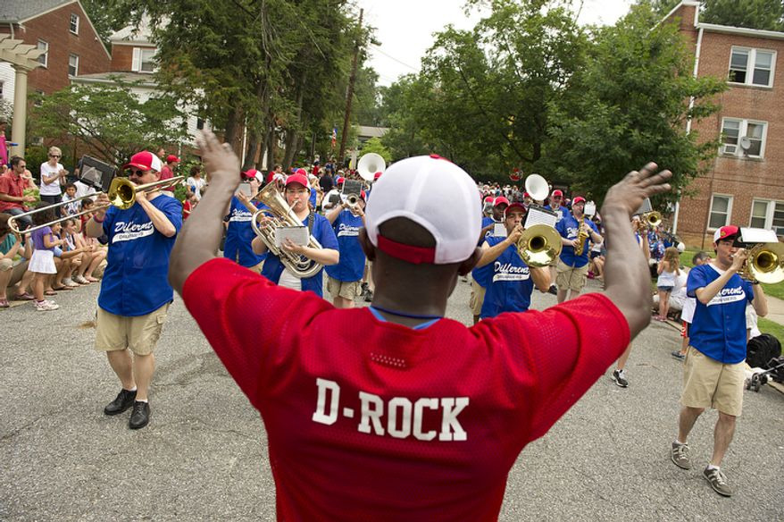 """""""D-Rock"""" conducts the Different Drummers band as they march in the 45th annual Palisades July Fourth parade. (Barbara L. Salisbury/The Washington Times)"""