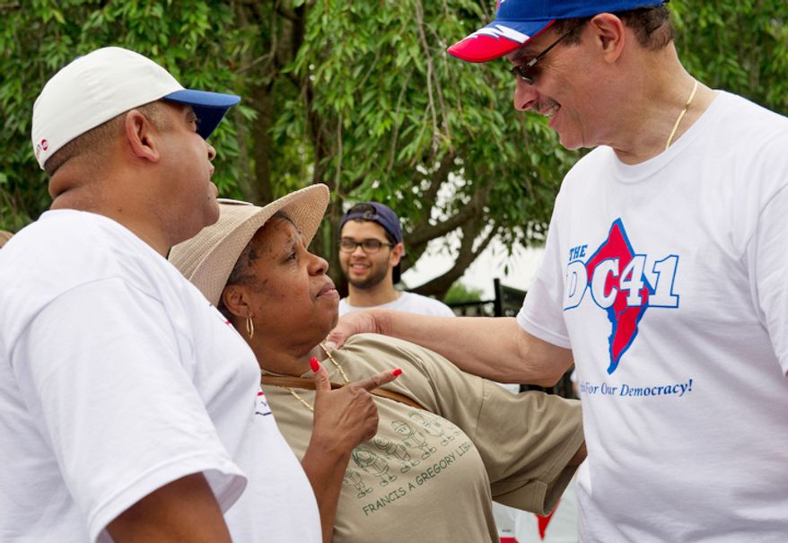 Carolyn Lynch (center), a resident of Washington's Ward 7, talks with Mayor Vincent C. Gray before he leaves the Palisades Recreation Center in Washington, which was the ending point of the Palisades July Fourthh parade.  (Barbara L. Salisbury/The Washington Times)