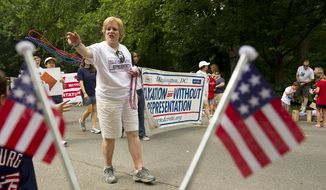 Annalee Ash of Washington tosses out red and blue beads to the crowd while marching with the Taxation Without Representation group in the 45th annual Palisades July Fourth parade in Washington on Monday, July 4, 2011. (Barbara L. Salisbury/The Washington Times) ** FILE **