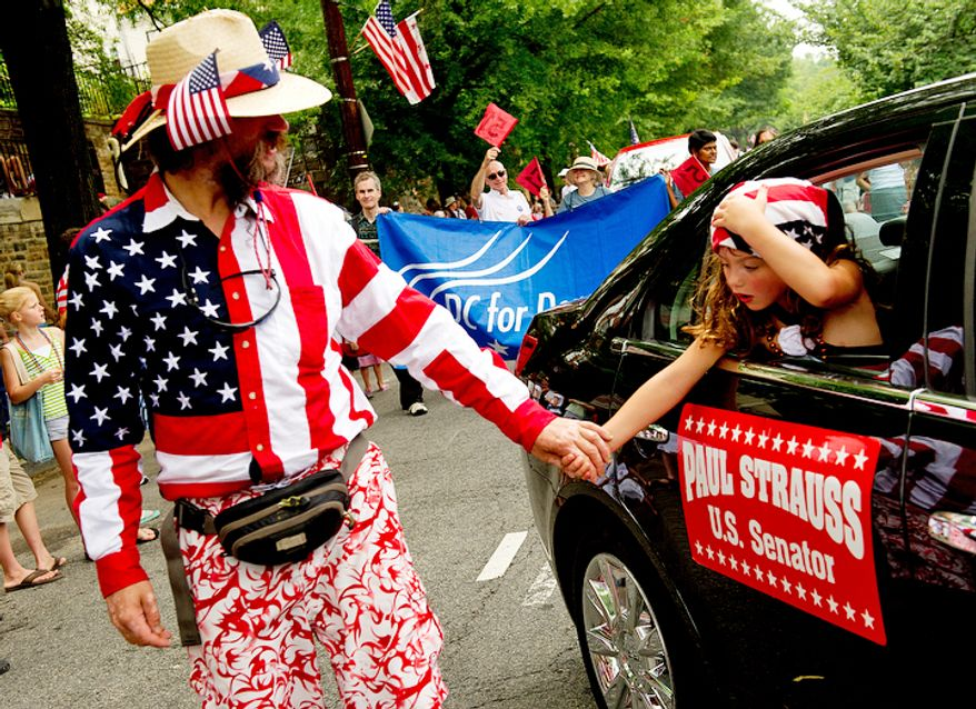 Juliet Houseknecht (right), 5, of Washington's Chevy Chase neighborhood reaches out of the car she's riding in during the Palisades July Fourth parade to hold her dad, Chad Houseknecht's hand. The two were participating in the parade with the Paul Strauss for U.S. Senate campaign contingent. (Barbara L. Salisbury/The Washington Times)