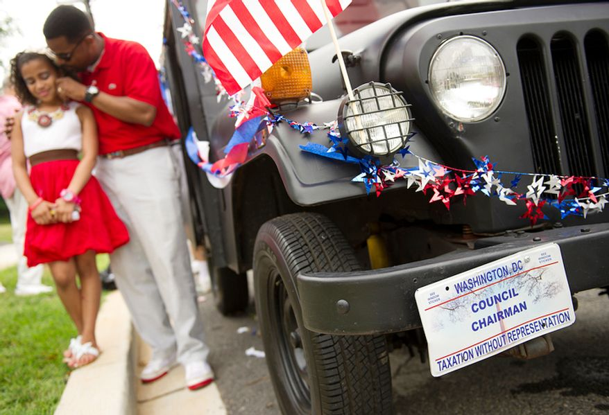 D.C. Council Chairman Kwame R. Brown has a tender moment with his daughter, 9-year-old Lauren, next to his black Jeep before the two march in the 45th annual Palisades July Fourth parade in Washington on Monday, July 4, 2011. (Barbara L. Salisbury/The Washington Times)