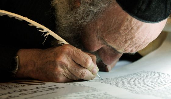 An ultra-Orthodox Jewish man writes some of the last words in a Torah scroll before it is taken from the Western Wall into the Hurva synagogue in Jerusalem's Old City. Software developed by an Israeli team of scholars is giving intriguing new hints about what researchers believe to be the multiple hands that wrote the Bible. (Associated Press)