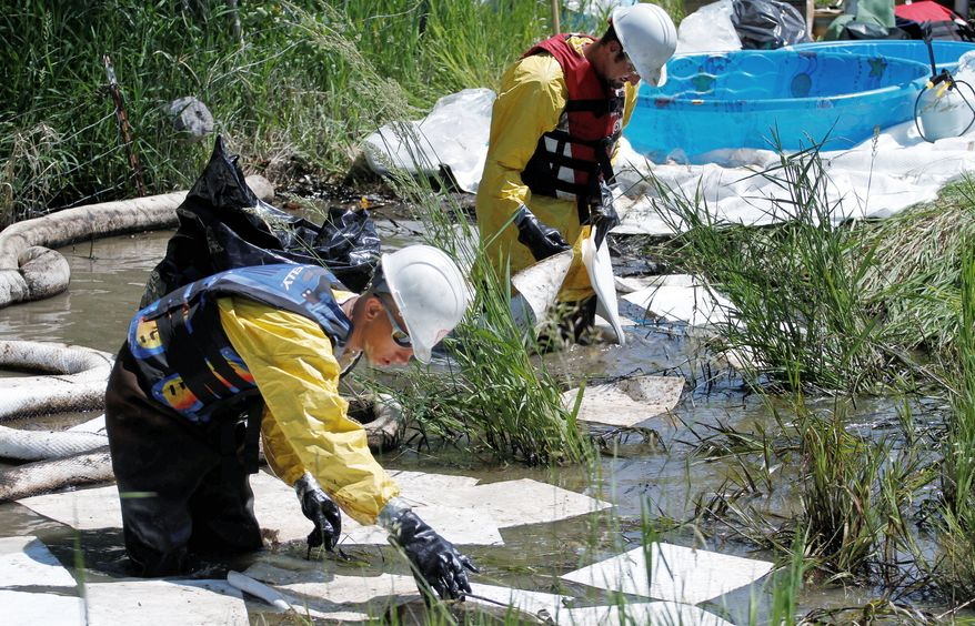 Cleanup crews clear oil from alongside the Yellowstone River in Laurel, Mont., on Tuesday, July 5, 2011. The scenic waterway has risen above flood stage, raising fears that the surging currents will further spread crude from the previous week's oil spill. (Associated Press)