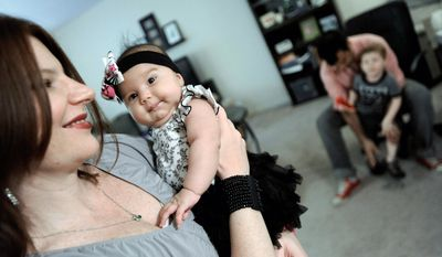"Gina Crosley-Corcoran holds 2-month-old daughter Jolene, born at home, while her husband, John, puts shoes on their son Jules 3. ""Women are finding that the hospital experience wasn't a good one,"" Mrs. Crosley-Corcoran said. (Associated Press)"