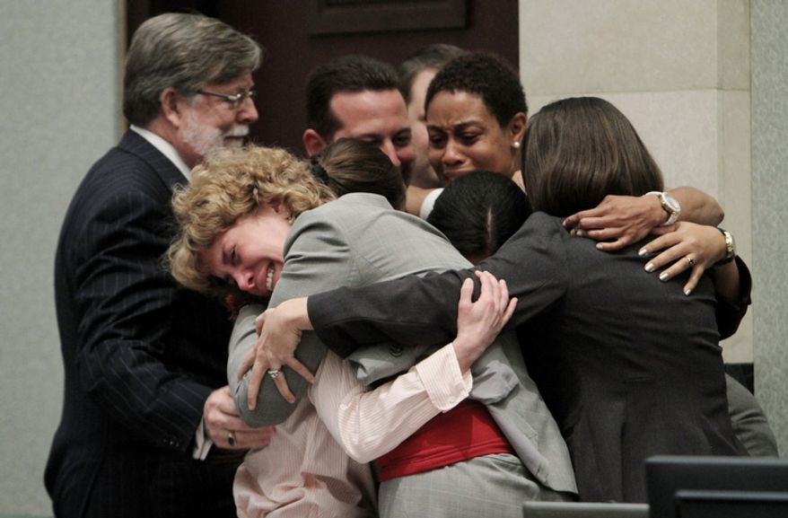 Defense attorney Dorothy Clay Sims, in gray jacket, covers her client Casey Anthony in a hug along with the rest of the defense team after Anthony was acquitted of murder charges. (AP Photo/Red Huber, Pool)