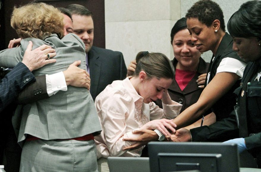 Casey Anthony, center, is overcome with as her lawyers, Jose Baez hugs Dorothy Clay Sims, left, after she was acquitted of murder charges. (AP Photo/Red Huber, Pool)