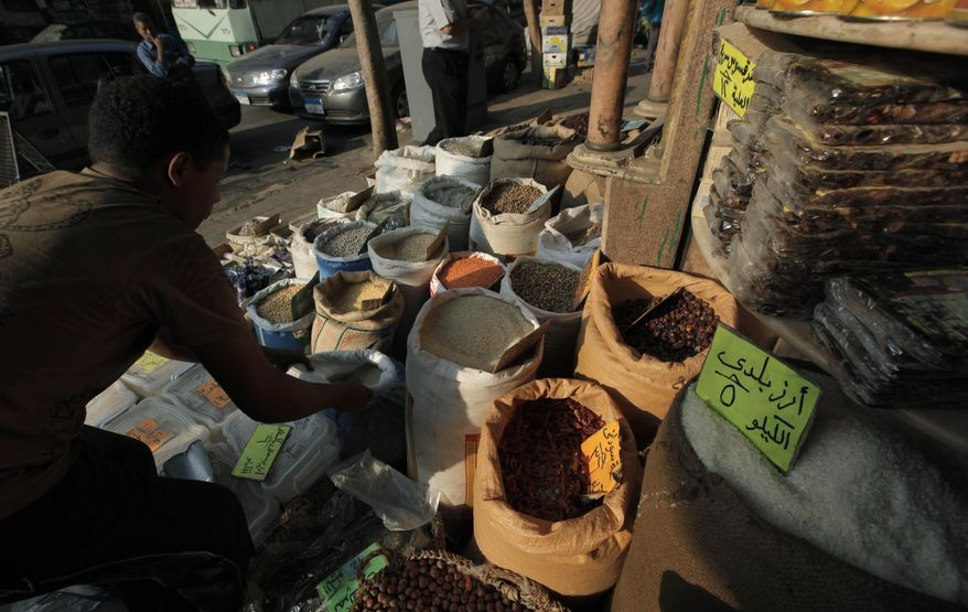 ** FILE ** An Egyptian spice dealer organizes products that include fenugreek seeds at his shop in Cairo on Thursday, June 30, 2011. The European Union on Tuesday temporarily banned the import of fenugreek seeds from Egypt after some were linked to a deadly outbreak of E. coli in Germany and France. (AP Photo/Nasser Nasser)