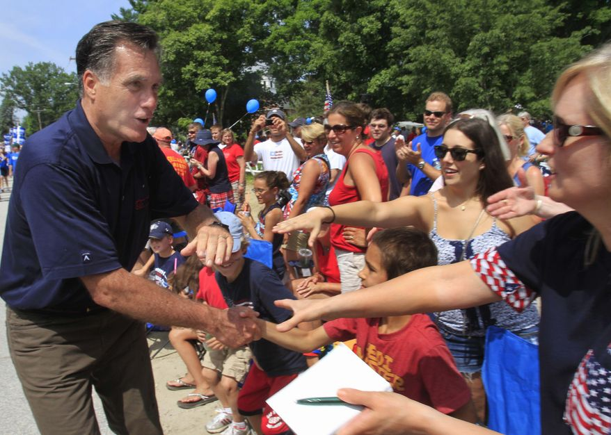 Republican presidential candidate and former Massachusetts Gov. Mitt Romney works the crowd as he marches in the Fourth of July parade in Amherst, N.H., on July 4, 2011. (Associated Press)