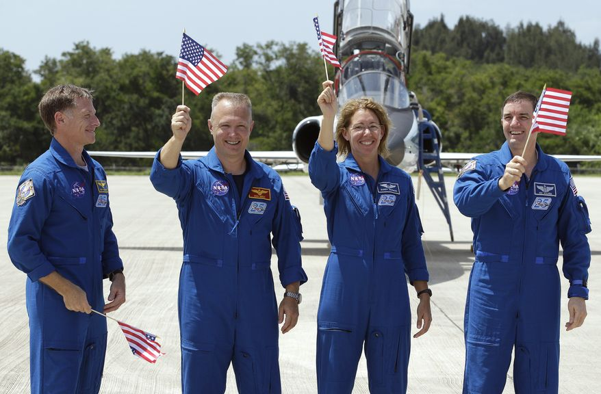 Astronaut Chris Ferguson (left), commander of the last space shuttle mission, looks on as his fellow crew members, (from left) pilot Doug Hurley and mission specialists Sandy Magnus and Rex Walheim, wave American flags after arriving at the Kennedy Space Center in Cape Canaveral, Fla., on Monday, July 4, 2011. The space shuttle Atlantis is scheduled to lift off Friday morning on a 12-day mission to the International Space Station. (AP Photo/Chris O'Meara)