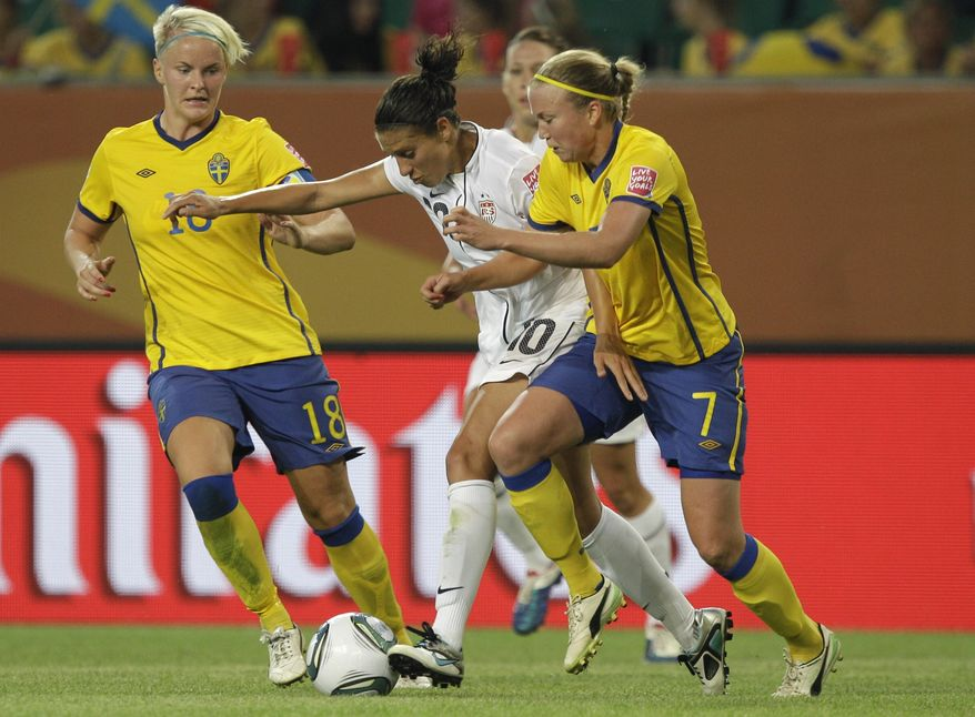 United States' Carli Lloyd, center, fights for the ball between Sweden's Nilla Fischer and Sweden's Sara Larsson, right, during the group C match between Sweden and the United States at the World Cup in Wolfsburg, Germany, on Wednesday. U.S. lost 2-1. (AP Photo/Marcio Jose Sanchez)