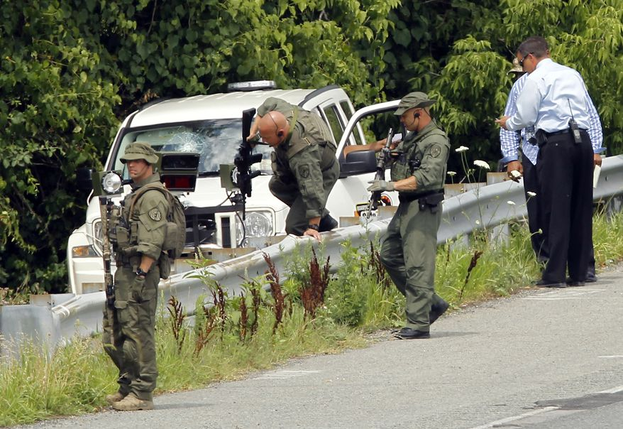 Law enforcement officials prepare to search the woods near a contractor's vehicle on Baltimore-Washington Parkway in Linthicum, Md., on July 6, 2011. Maryland State Police and Anne Arundel County police are searching for an armed man along the parkway who hit the windshield of a contractor's vehicle with a hammer before fleeing. (Associated Press)