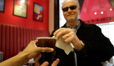 This Wednesday, April 27, 2011 photo shows customer Brad Shaffer as he is served an iced coffee at Cafe Madeleine in San Francisco. (AP Photo/Eric Risberg)