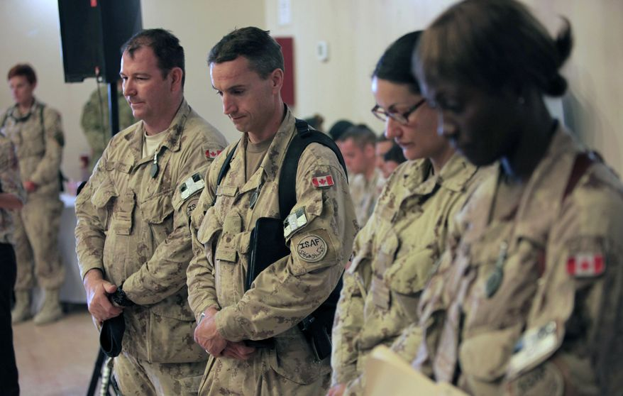Canadian soldiers pay tribute to their fallen comrades during a transfer-of-command ceremony at Kandahar Airfield in Afghanistan on Thursday, July 7, 2011. (AP Photo/Rafiq Maqbool)