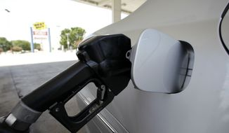 A gasoline pump fills up a vehicle. (Associated Press)**FILE**