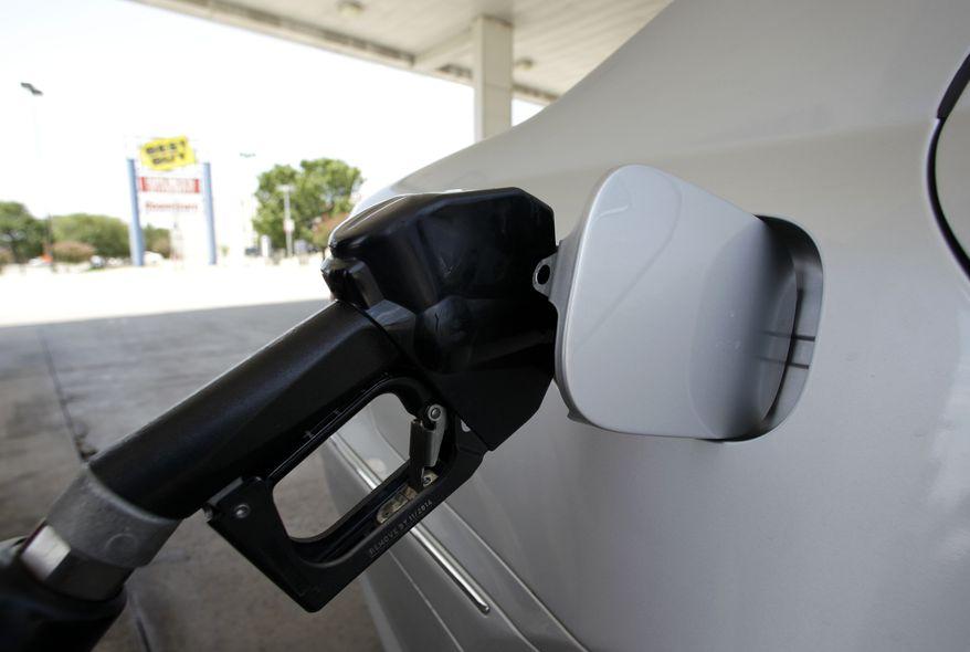 A gasoline pump fills up a vehicle. (Associated Press)**FILE**