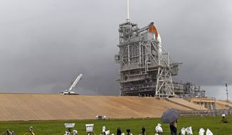The space shuttle Atlantis sits on the launch pad as a rain cloud passes the Kennedy Space Center in Cape Canaveral, Fla., on Thursday, July 7, 2011. (AP Photo/Terry Renna)