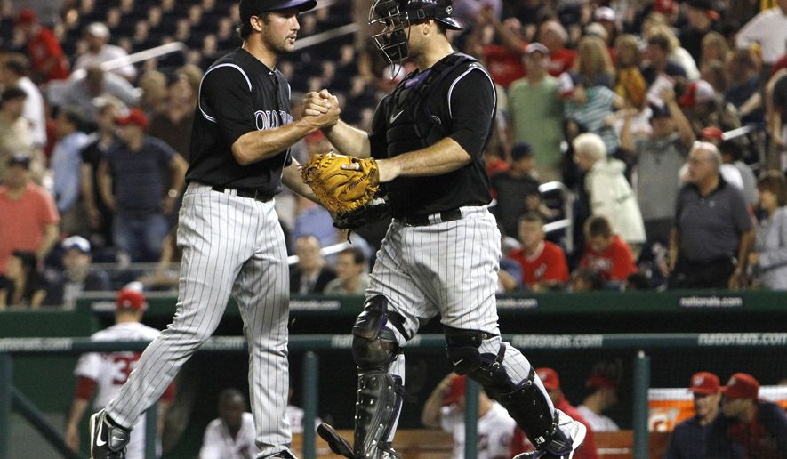 Colorado Rockies relief pitcher Huston Street congratulates catcher Chris Iannetta, after they won their baseball game against the Washington Nationals 3-2 at Nationals Park on Friday. (AP Photo/Jacquelyn Martin)
