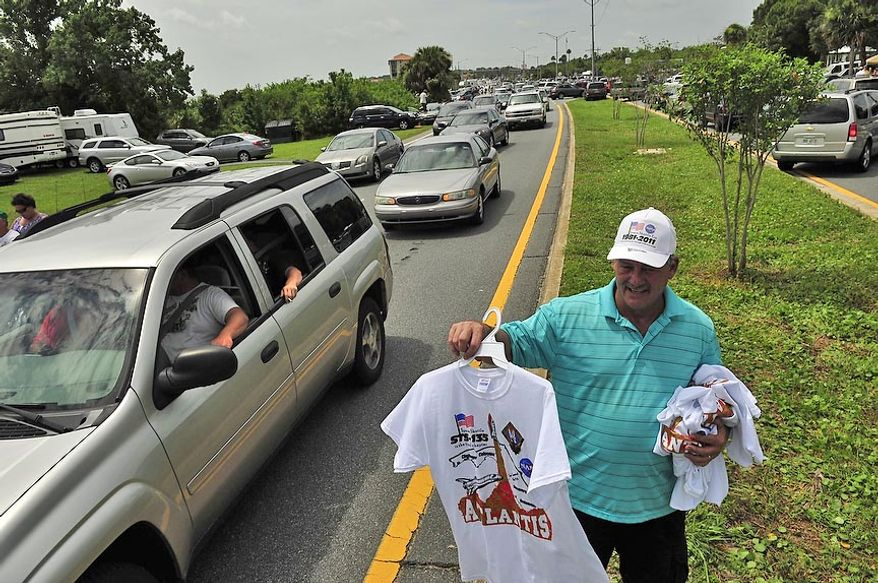 Donnie Green of Sanford, Fla., sells T-shirts on Friday, July 8, 2011, to drivers and passengers stuck in traffic on Route 1 in Titusville, Fla., following the launch of the space shuttle Atlantis at the Kennedy Space Center. (J.M. Eddins Jr./The Washington Times)