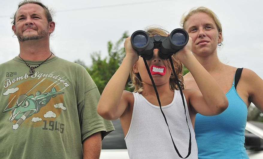 Kayn Clark (center), 10, of Clearwater, Fla., and his parents, Daniel and Brandi Clark, watch from the roadside on Friday, July 8, 2011, as the space shuttle Atlantis launches from Pad 39A at the Kennedy Space Center, about seven miles away. (J.M. Eddins Jr./The Washington Times)