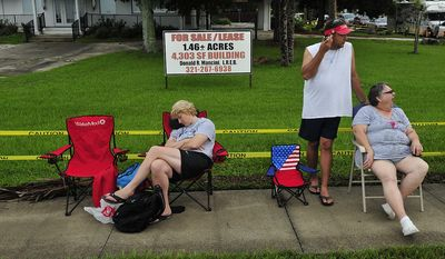 Dana Frentz (left) of Raleigh, N.C., sleeps on Friday, July 8, 2011, next to Bryan DuBray (center) and his mother, Charlotte DuBray, both of Houston, along the roadside in Titusville, Fla., while waiting to watch the space shuttle Atlantis launch from the Kennedy Space Center, about seven miles away. (J.M. Eddins Jr./The Washington Times)