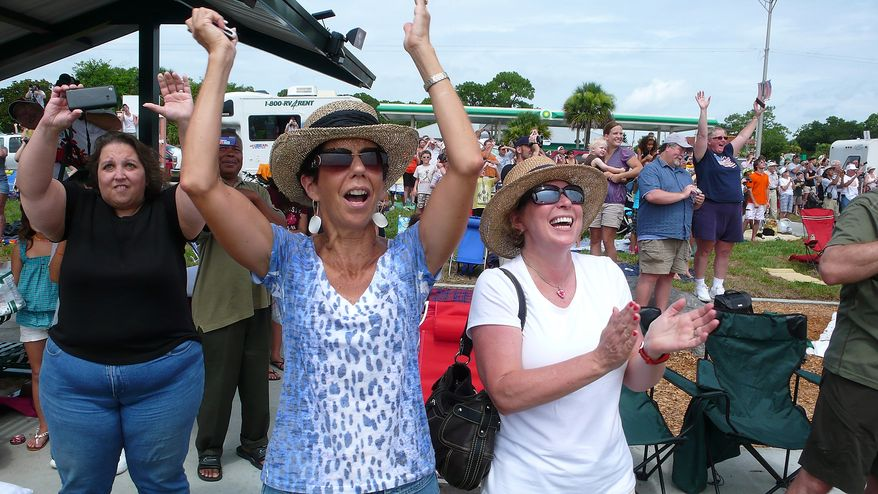 Denise McCabe (left center) of Vero Beach, Fla., and Cheryl Giesa (in white shirt) of Northville, Mich., cheer on Friday, July 8, 2011, as they watch from the roadside in Titusville, Fla., as the space shuttle Atlantis launches from Pad 39A at the Kennedy Space Center, about seven miles away. (J.M. Eddins Jr./The Washington Times)