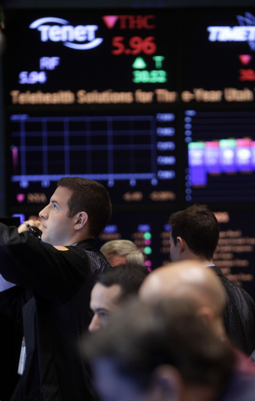 **FILE** In this photo from June 27, 2011, traders work on the floor at the New York Stock Exchange in New York. (Associated Press)