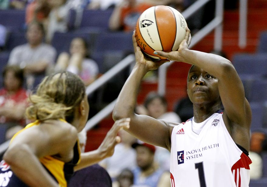 FILE - In this June 21, 2011, file photo, Washington Mystics' Crystal Langhorne, right, shoots the ball over Indiana Fever's Tamika Catchings during the fourth quarter of a WNBA basketball game in Washington. The Mystics lost 68-57 to the Fever on Saturday. (AP Photo/Luis M. Alvarez, File)