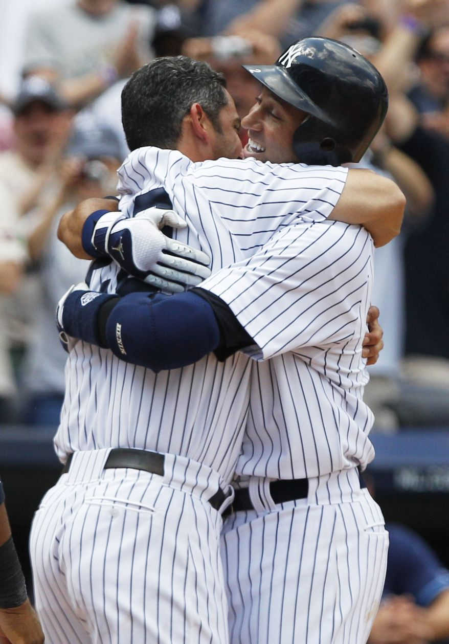 New York Yankees' Derek Jeter, right, hugs teammate Jorge Posada after hitting a home run for his 3,000th career hit during the third inning of a baseball game against the Tampa Bay Rays, Saturday, July 9, 2011, at Yankee Stadium in New York. Jeter became the 28th major leaguer to hit the milestone and also the first Yankees player. (AP Photo/Frank Franklin II)