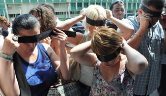 Georgian journalists blind-fold themselves before forming a human chain around the Interior Ministry office in Tbilisi on Friday. The Center for Human Rights in Tbilisi said recent detention of members of the media were an attack on media freedoms and demanded the release of three detained photographers. (Associated Press)