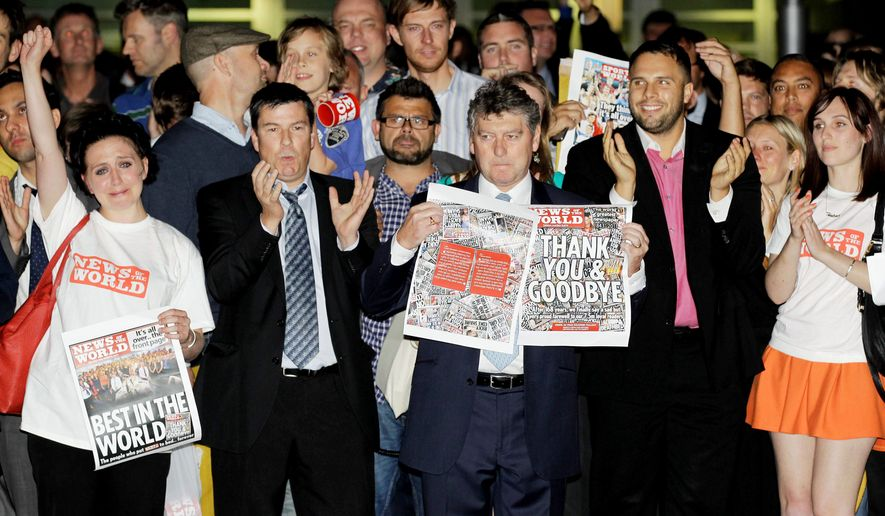 ** FILE ** News of the World Editor Colin Myler (center) holds a copy of the paper's last issue as he leads his staff out of the headquarters of News International in London on Sunday, July 10, 2011. (Associated Press)