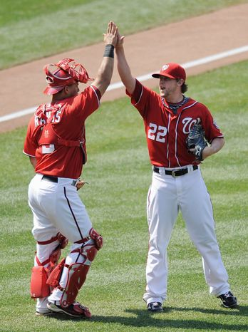 Closer Drew Storen (22) and catcher Wilson Ramos celebrate after the Nationals won 2-0 to avoid a three-game sweep  by the Rockies. Washington is 46-46 at the All-Star break. (Associated Press)