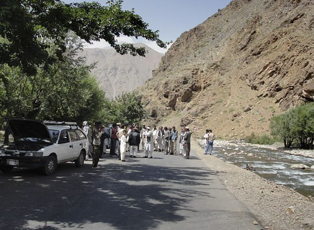 Afghans stand at the scene where a guard opened fire at a NATO-escorted reconstruction convoy in Dara, Panjshir province, north of Kabul, Afghanistan, on Saturday, July 9, 2011. The shooter killed a NATO service member and a civilian working for the coalition before being killed by return fire, the provincial police chief said. (AP Photo)