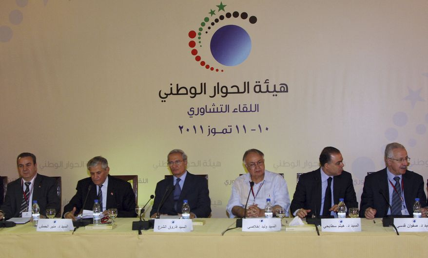 "Syrian Vice President Farouk al-Sharaa (third from left), with less prominent opposition figures, attends the opening session of government-sponsored reform talks in Damascus, Syria, on Sunday, July 10, 2011. The banner reads, ""National dialogue consultative meeting, July 10-11, 2011."" (AP Photo/Bassem Tellawi)"