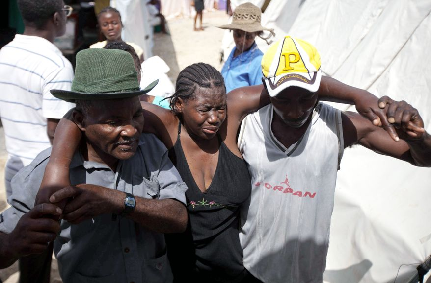A woman weakened by cholera symptoms is carried to the treatment center in Mirebalais, a town that is a one-hour drive north of Port-au-Prince. Cholera is relatively easy to treat if people can get help in time. A public health campaign has featured radio jingles and text messages to educate people about the disease. (Associated Press)