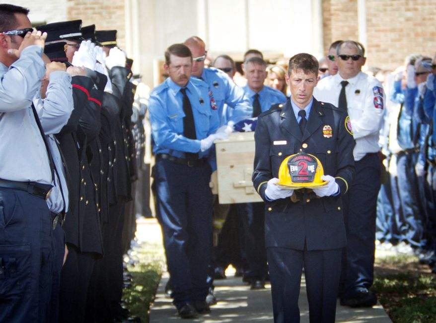 Conroe Fire Department's Greg Nesom carries the helmet of Shannon Stone as he leads the casket from the church at the funeral for  firefighter Lt. Stone, in Brownwood, Texas, on Monday, July 11, 2011. Stone fell to his death while trying to catch a souvenir baseball at a Texas Rangers game. (AP Photo/Star-Telegram, Joyce Marshall)