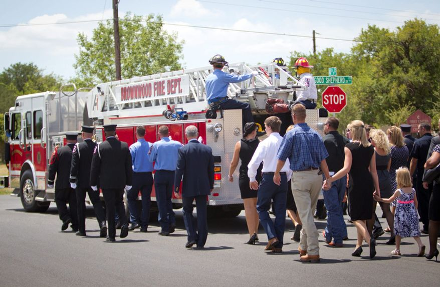 Family members follow the procession with the fire truck carrying the casket of Brownwood firefighter Lt. Shannon Stone after the funeral in Brownwood on Monday, July 11,  2011.  (AP Photo/Star-Telegram, Joyce Marshall)