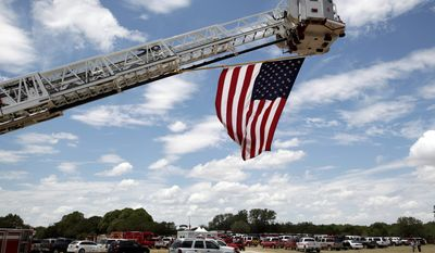 An American flag hangs off the back of a ladder truck as emergency vehicles fill the parking area at a cemetery during the service for Lt. Shannon Stone of the Brownwood Fire Department Monday, July 11, 2011, in Brownwood, Texas.  Stone was fatally injured trying to catch a souvenir baseball at a Texas Rangers game. (AP Photo/Tony Gutierrez)