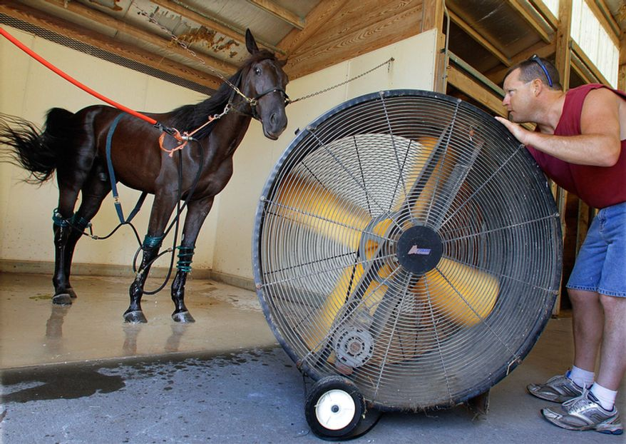 Mike Cox, of Sherman, Ill., positions a large fan and specially designed water hoses to cool his Standardbred trotting filly named Master Charge It, Monday, July 11, 2011, at the Illinois State Fairgrounds in Springfield, Ill.  Around the country temperatures have been reaching 100 degrees.  (AP Photo/Seth Perlman)