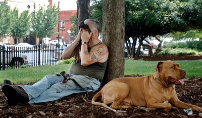 Frank Milo cools down under the shade of a tree on the University of Georgia's North Campus along with his dog, Milo, on Monday, July 11, 2011 in Athens, Ga.  (AP Photo/Athens Banner-Herald, Fei Y. Chen)  MAGS OUT; MANDATORY CREDIT; NO SALES