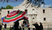 A vendor near the Alamo opens a umbrella to provide protection from the sun, Monday, July 11, 2011, in San Antonio, Texas. (AP Photo/Eric Gay)