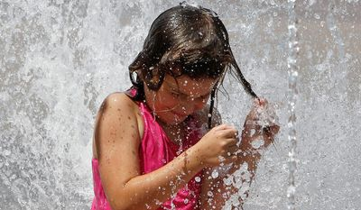 Sarah McCain, 8 of Willow Park, plays in a fountain in front of the National Cowgirl Museum and Hall of Fame. (AP Photo/The Fort Worth Star-Telegram, Richard W. Rodriguez)  MAGS OUT