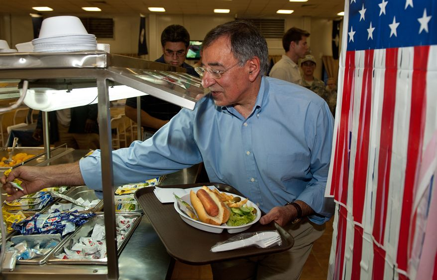 Secretary of Defense Leon E. Panetta reaches for packets of mustard and relish as he takes a hot dog for lunch during his visit to Camp Victory in Baghdad on Monday, July 11, 2011. (AP Photo/Paul J. Richards, Pool)