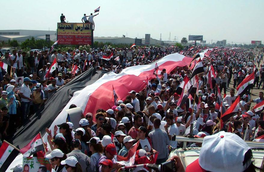 ** FILE ** In this photo released by the Syrian official news agency SANA and according to them, thousands of supporters of Syrian President Bashar Assad, carry a gigantic 17,500 yards (16,000 meters) Syrian flag during a pro-Assad demonstration, in the Mediterranean city of Latakia, northewest of Damascus, Syria, on Sunday, July 10, 2011. (AP Photo/SANA)