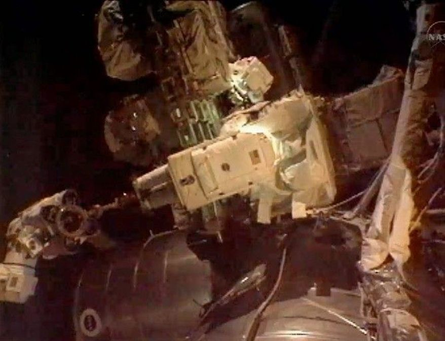 ASSOCIATED PRESS Astronauts Ronald Garan Jr. (top) and Michael Fossum work outside the International Space Station during the last spacewalk of NASA's space- shuttle era on Tuesday. They retrieved a broken ammonia pump.